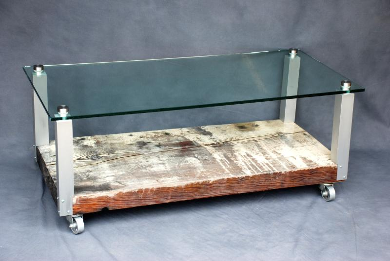 A coffee table of reclaimed, distressed fir coated with gloss epoxy on a base of aluminum with a glass top and casters.