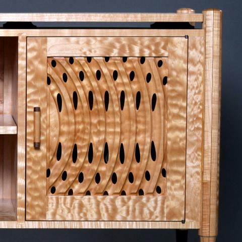 Intricately carved cabinet door in curly maple